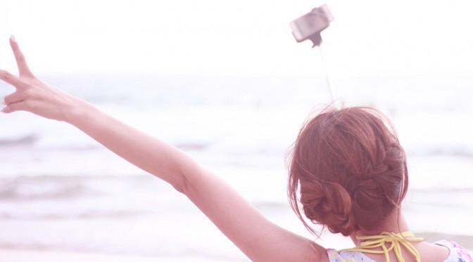自撮り棒で写真を撮る女性