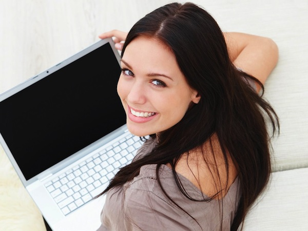 Top view of a young woman sitting on floor with a laptop and looking up